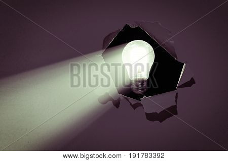 The concept of a new idea. Electric bulb emits a beam of light through a hole in the paper.