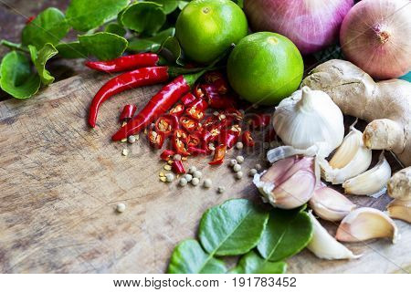 Food ingredient ginger chili pepper lime and garlic on wooden table asian food cooking concept.