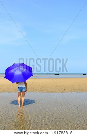 Southeast asia women with umbrella stand on the beach under the sun light