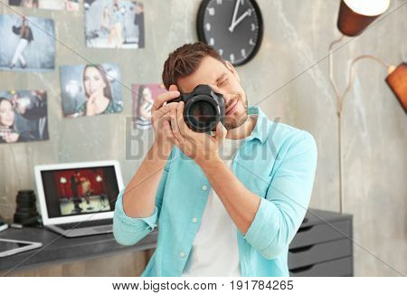 Young photographer with camera in office