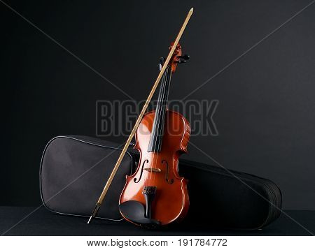 Classical wooden Violin with molded carrying black case. Musical string instrument fiddle with violin bow isolated on black background.