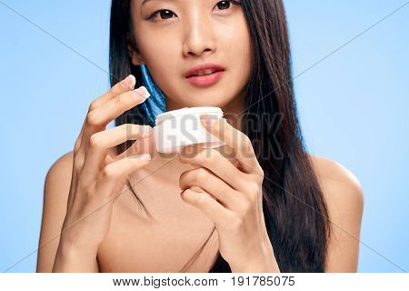 Woman with cream, facial, woman on blue background portrait.