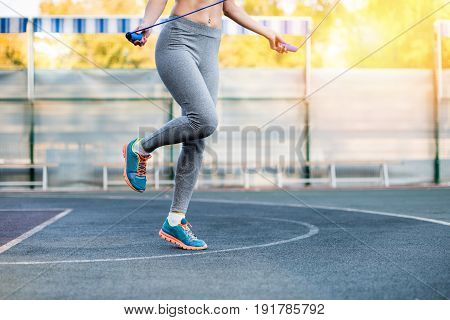 Low Section Of Young Sporty Woman Training With Skipping Rope On Stadium