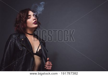 Beautiful young female in black bra and leather coat breathing out smoke on black background.
