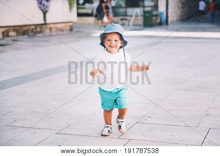 Cute little boy run on a city street. Happy smiling child. It is summer time! Kid in summer clothes in vacation with family.