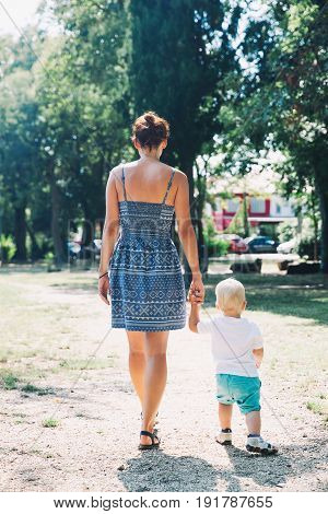 Beautiful young woman and her child spend time in the park at summer time. Family Lifestyle background concept. Back view. Mother and son walking outdoors on the nature background.