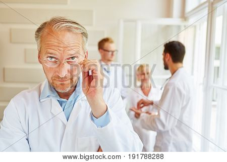 Doctor as chief physician with glasses looking spektical