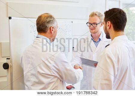 Senior doctor congratulates with handshake for successful teamwork