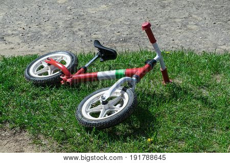 On the playground the grass is a children's balance bike. Balance bike for training exercise and physical activity of children. Useful for health.