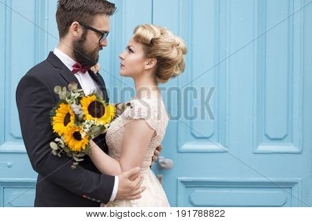 Newlywed couple standing next to a blue retro wooden door holding a sunflower wedding bouquet and looking at each other