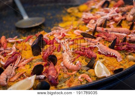 Street food in San Fermin feast, Pamlona, Navarra, Spain. Paella. Rise with seafood and vegetables. Spanish traditional cuisine. Spanish national dish.