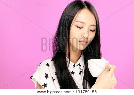 Woman looking at mug, woman with mug, woman on pink background.