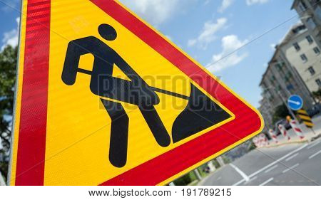 Road works sign closeup. Traffic sign construction sign and worker