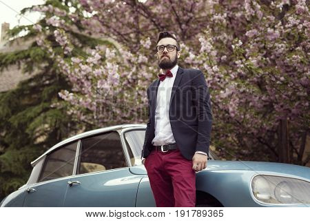 Hipster groom standing in the street next to an old retro car ready to embark on a honeymoon