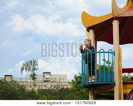 Child blow bubbles with height. High Playground sky house