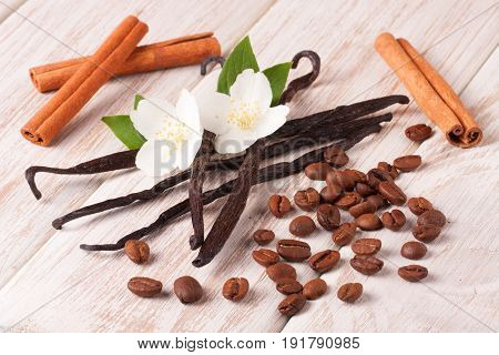 Vanilla sticks and coffee beans with cinnamon on a white wooden background.