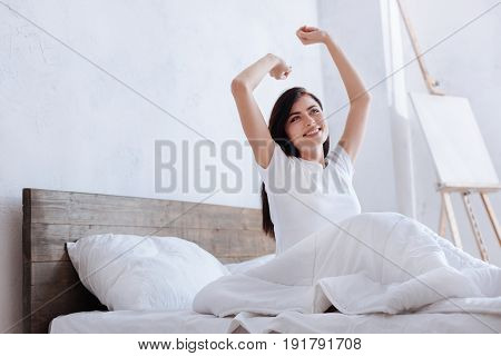 The work is waiting. Shot of a chestnut haired woman covered in a blanket while sitting on a bed with her arms outstretched.