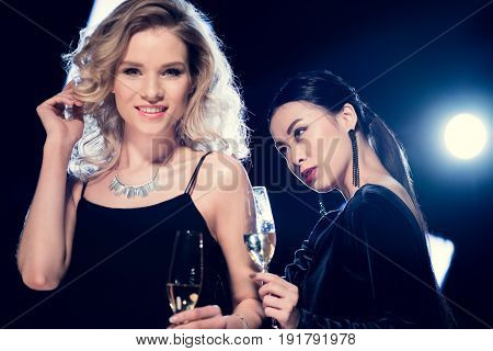 Attractive Glamour Multicultural Girls Wearing Evening Gowns And Holding Champagne Glasses At Party