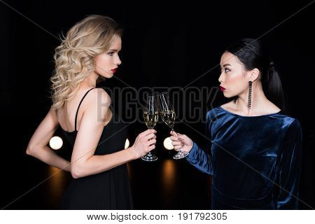 Young Glamour Girls In Evening Gowns Clinking With Champagne Glasses At Party