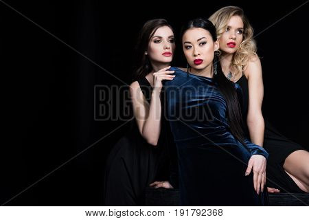 Young Glamorous Multiethnic Women Posing At Dark Evening Gowns