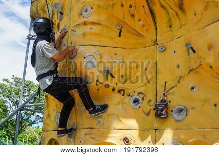Labuan,Malaysia-May 21,2017:Muslim woman with safety equipment climb on climbing wall in Labuan,Malaysia.It is an activity in which participants climb up,down or across artificial rock walls