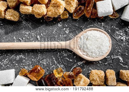 lumps of sugar with spoons sweet set on dark kitchen table background top view pattern
