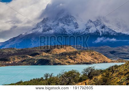 The magnificent cliffs of Los Cuernos in the clouds are covered with snow. Torres del Paine National Park. Summer in the south of Chile. The concept of extreme and active tourism