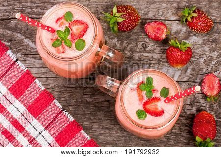 Glass of strawberry yogurt or smoothie with mint leaves on old wooden background. Top view.