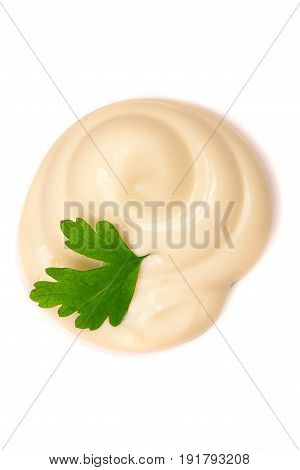 Mayonnaise swirl with a parsley leaf isolated on a white background close-up. Top view.