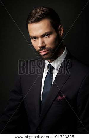 Handsome young businessman portrait on black background. Smart boss, manager