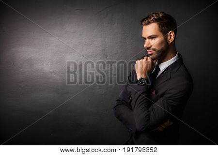 Young businessman thinking about new business ideas. Black background copy-space.