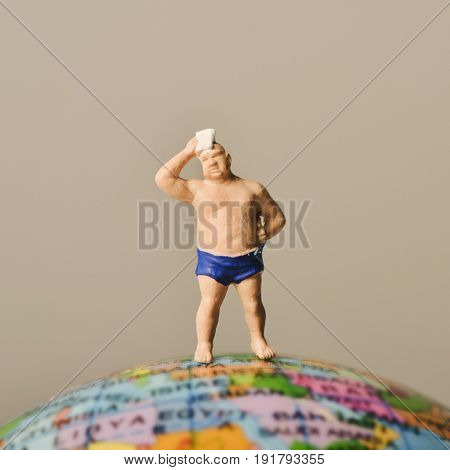 a miniature man wearing swimsuit and drying his forehead with a handkerchief on the top of the terrestrial globe