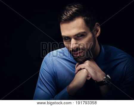 Young businesman portrait on black background. Intense, confident look