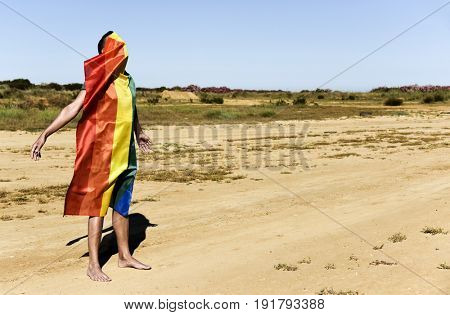 a barefoot young caucasian man covered with a rainbow flag in a natural landscape