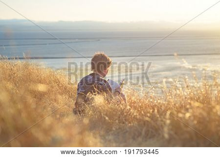 Boy reading book in yellow grass high in the hills, watching beautiful sunset above Bay Area, rear view