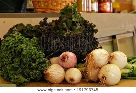 Onion bulbs and green leafy vegetables Freshly harvested onions and green vegetables set on a table for sale