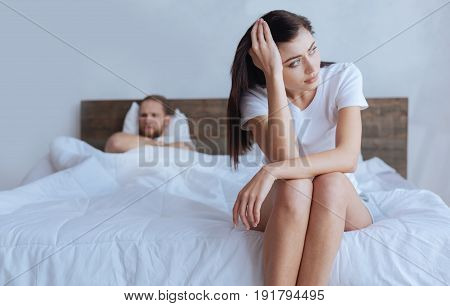 Why cannot we live in peace. Young couple sitting on a bed separately after having an argument together.