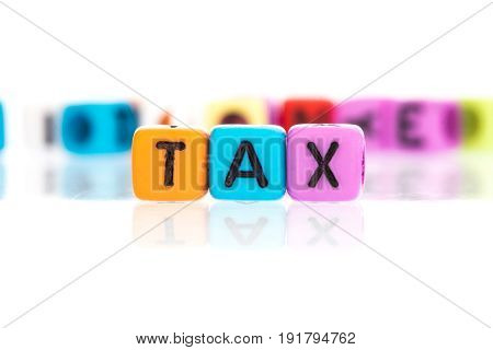 colorful word cube of TAX on a white background