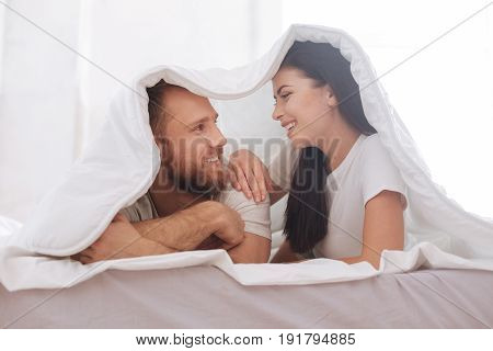 Cannot imagine my life without you. Radiant couple smiling while lying on a bed underneath a blanket and maintaining an eye contact.