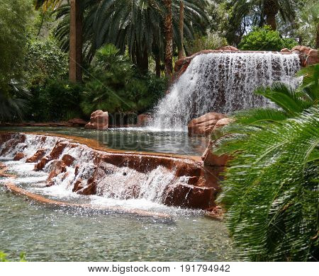Two tiers of man-made waterfalls  Water cascades down two tiers of waterfalls from a landscaped garden