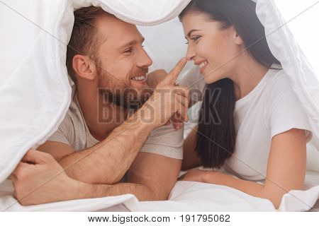 Got your nose. Adorable young couple lying underneath the blanket and having a pillow talk while a man touching his wife nose.