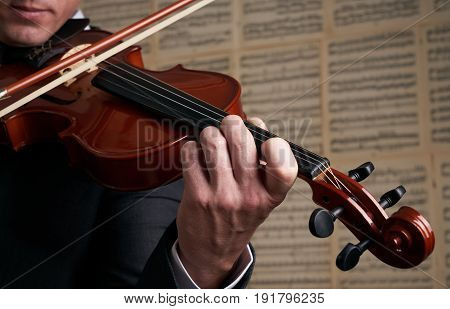 Violin player hands. Musician virtuoso violinist playing violin against the background of musical notes. Close up of musical instruments fiddle with fiddlestick