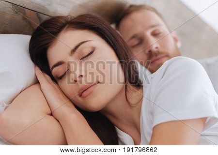 Bedtime stories. Adorable newly married husband and wife sleeping together in bed after a long working day.