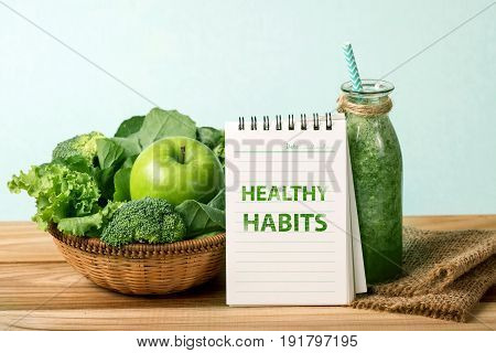 HEALTHY HABITS message and the Healthy fresh green smoothie juice in glass bottle on wooden table with green apple and vegetables basket for healthy detox and diet habits concept