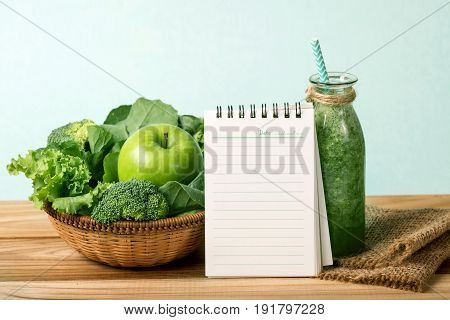 blank note pad and the Healthy fresh green smoothie juice in glass bottle on wooden table with green apple and vegetables basket for healthy detox and diet habits concept
