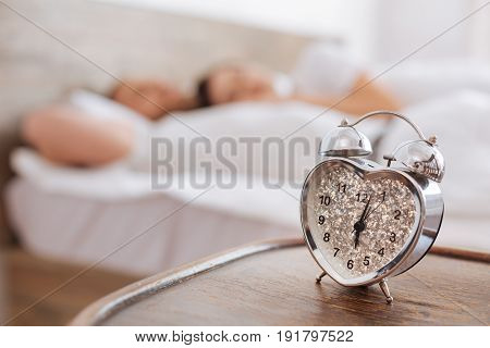 Waking them up. Close up of a heart shaped alarm clock standing on a chair with a young couple enjoying their last minutes of sleep.