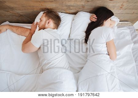 Sleeping soundly. Millennial man and woman having a nap together and resting in bed while sleeping tight.