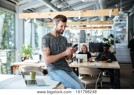 Photo of happy young man sitting on table in office chatting by phone. Looking aside.