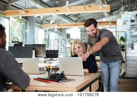 Picture of cheerful young colleagues sitting in office coworking using laptop computers. Looking aside.