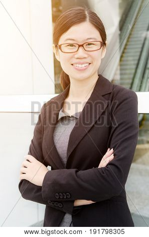 Asian executive arms folded smiles and standing outdoors